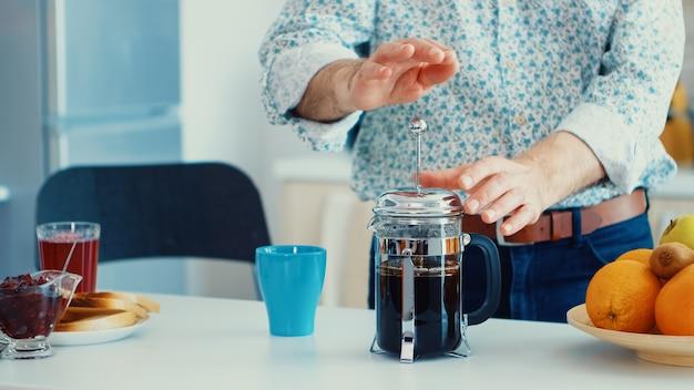Uomo anziano che fa il caffè usando la stampa francese per la colazione in cucina. la persona anziana al mattino si gode la caffeina della tazza di caffè espresso marrone fresca dalla tazza vintage, il filtro rilassa il rinfresco