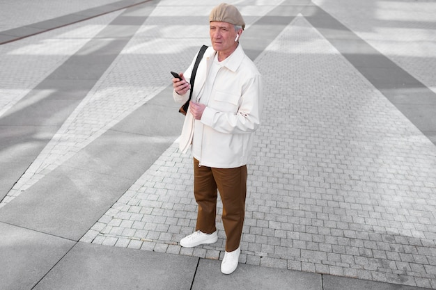Пожилой мужчина на улице в городе с помощью смартфона с наушниками Бесплатные Фотографии
