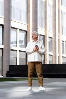 Пожилой мужчина на улице в городе с помощью смартфона с наушниками