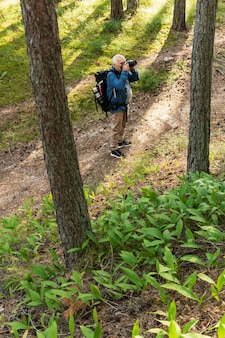Older man photographic nature while backpacking