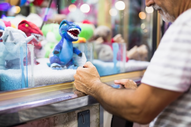 Older man playing toy claw machine