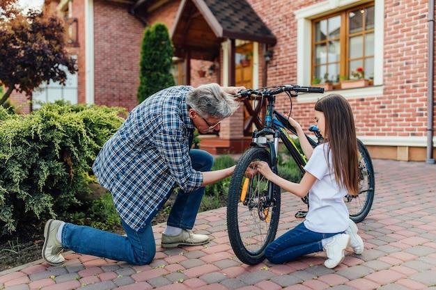 彼の子供のために自転車を修理する年配の男性。ホームタイム、休憩のコンセプト。 無料写真