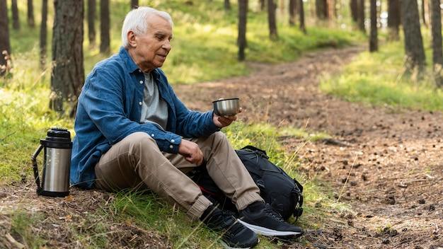 Uomo anziano che riposa mentre si viaggia nella natura