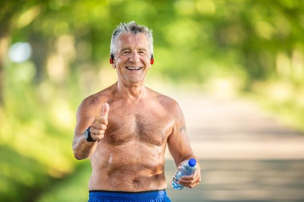 Пожилой мужчина показывает палец вверх, держа воду в бутылках и не одетый в футболку после тренировки
