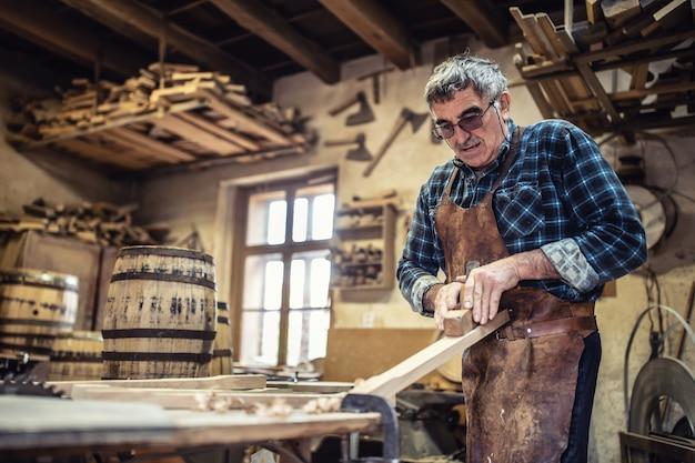 노인은 목재 통을 만들기 위해 목재를 사용하기 전에 목재의 표면을 부수고 있습니다.