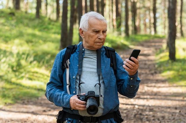 カメラとスマートフォンで自然の中で旅行する年上の男