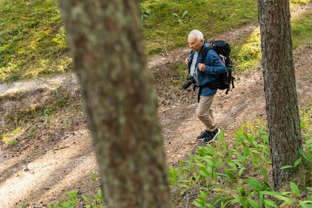 Older man traveling in nature with backpack