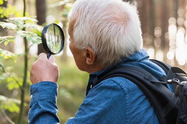 Older man traveling outdoors and using magnifying glass