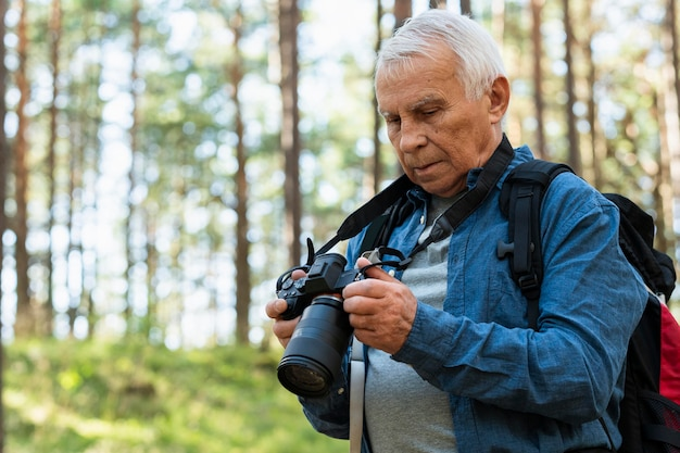 Older man traveling outdoors with camera