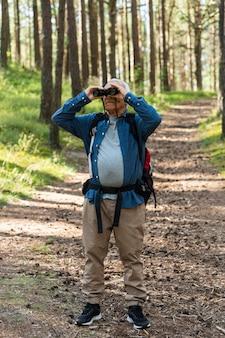 Uomo più anziano che utilizza il binocolo durante lo zaino in spalla nella natura