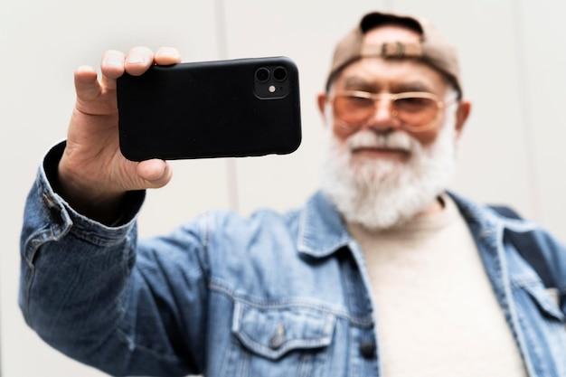 都会の屋外でスマートフォンを使って自撮りをする老人