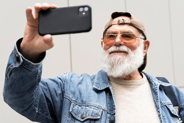 Пожилой мужчина с помощью смартфона для селфи на открытом воздухе в городе