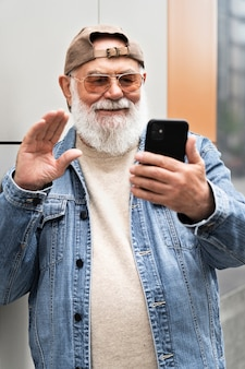 Older man using smartphone outdoors in the city for video call