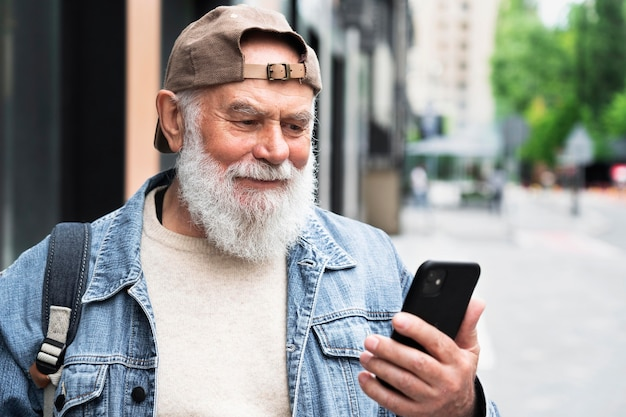 Older man using smartphone outdoors in the city