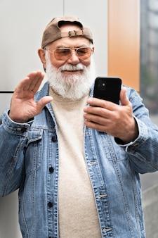 화상 통화를 위해 도시에서 야외에서 스마트 폰을 사용하는 노인