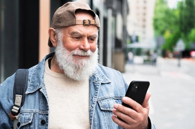 Пожилой мужчина с помощью смартфона на открытом воздухе в городе