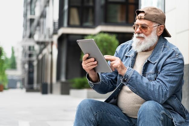 Uomo anziano che utilizza tablet all'aperto in città
