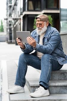 Пожилой мужчина с помощью планшета на открытом воздухе в городе Бесплатные Фотографии