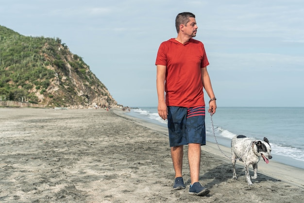 Пожилой мужчина выгуливает собаку утром на пляже