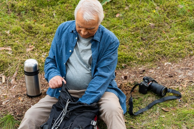 Older man with backpack and camera resting while exploring nature