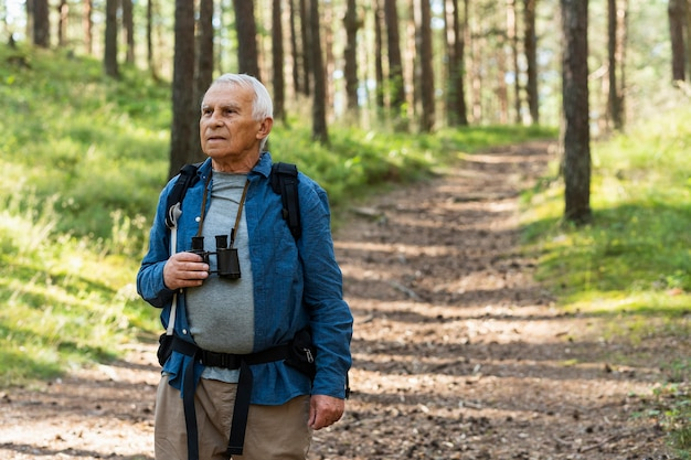 Older man with binoculars and backpack exploring nature