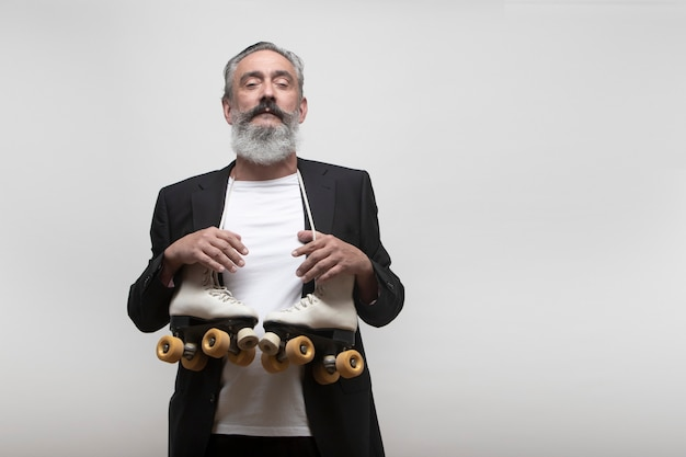 Older man with blazer and roller skates hanging from his neck on a white background