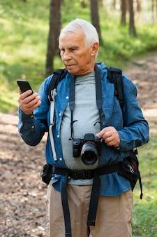 自然の中で屋外でカメラとスマートフォンを持つ老人