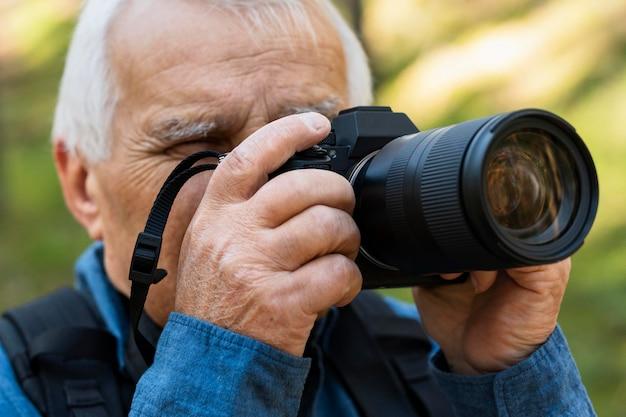 Uomo più anziano con la macchina fotografica all'aperto nella natura