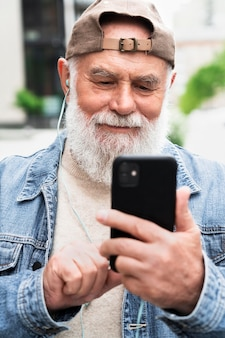 Older man with smartphone outdoors in the city