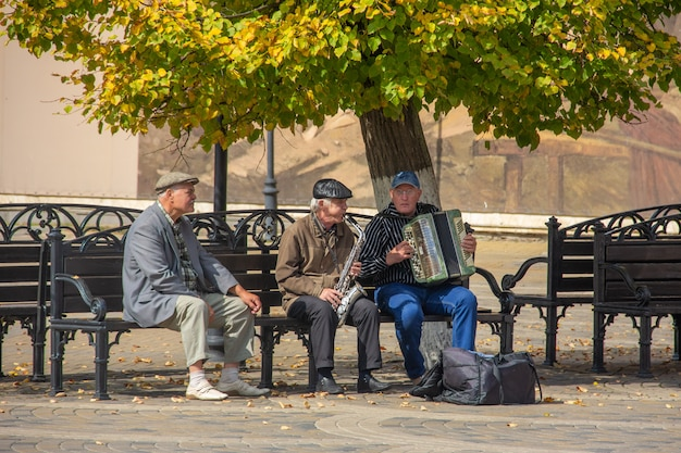 Older men sit on a bench in the park and play musical instruments in autumn sunny day