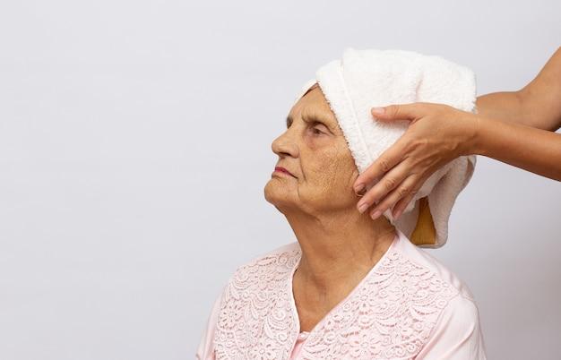 샤워 후 머리에 수건을 얹은 나이 많은 좋은 여자