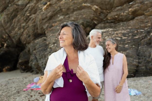 Пожилые люди на пляже вместе проводят время