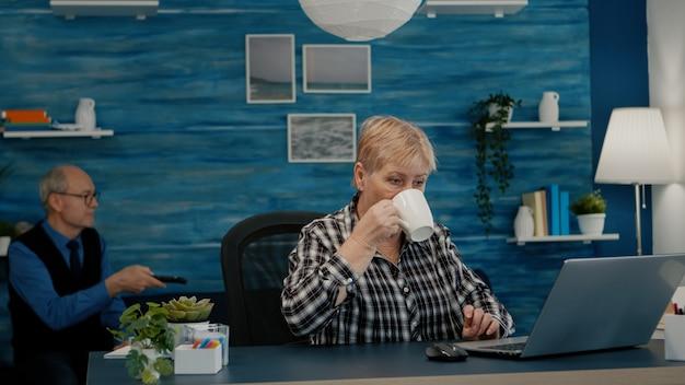 Donna d'affari matura professionale anziana che utilizza laptop seduto alla scrivania del posto di lavoro a bere caffè