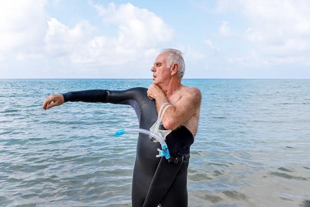 수영을 하러 해변에서 잠수복을 입은 은퇴한 노인.