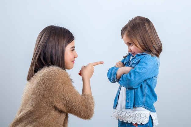 Older sister gives a remark to the younger one with a finger.