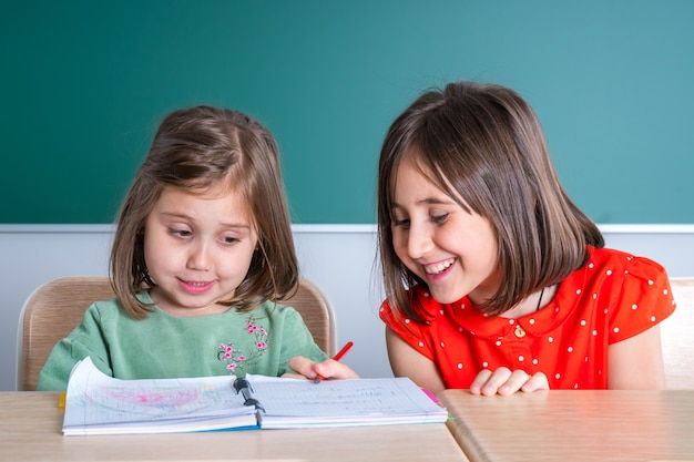Older sister looks at her younger sister as she draws in a notebook.