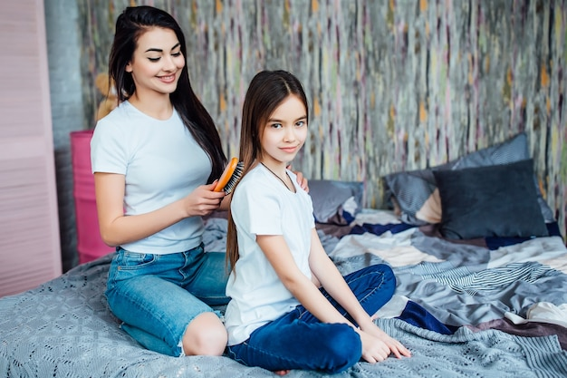 Older sister preparing little to school and combing her hair in bedroom with hairbrush