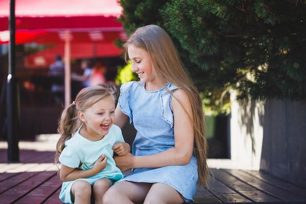 Older sister tickles younger sister on the veranda in the park