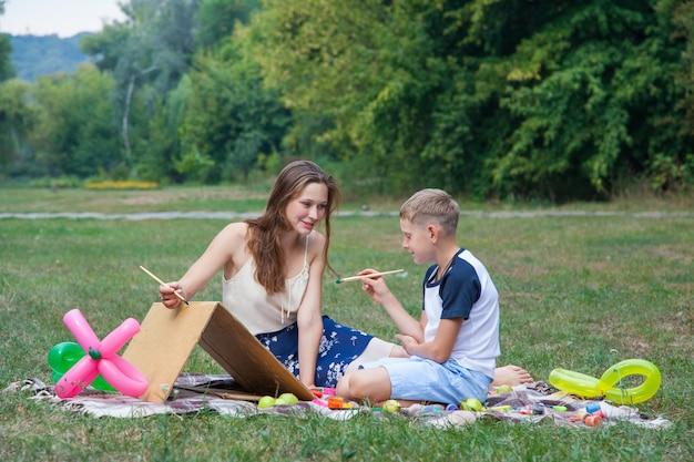 兄に公園で絵を描くように教えようとしている姉