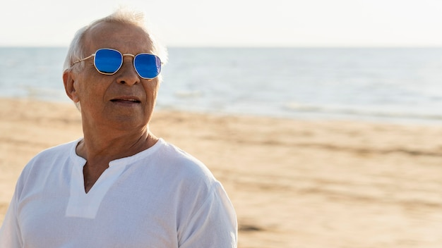 Older stylish man with sunglasses posing by the beach
