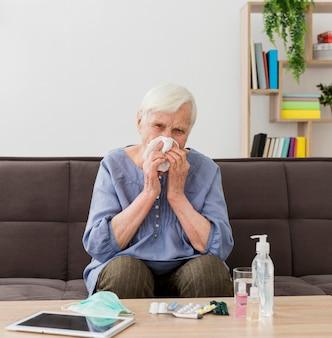 Пожилая женщина дома сморкается