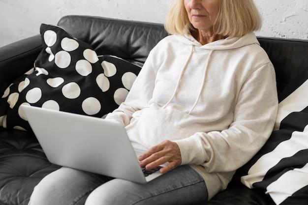 Пожилая женщина дома на диване, работает на ноутбуке