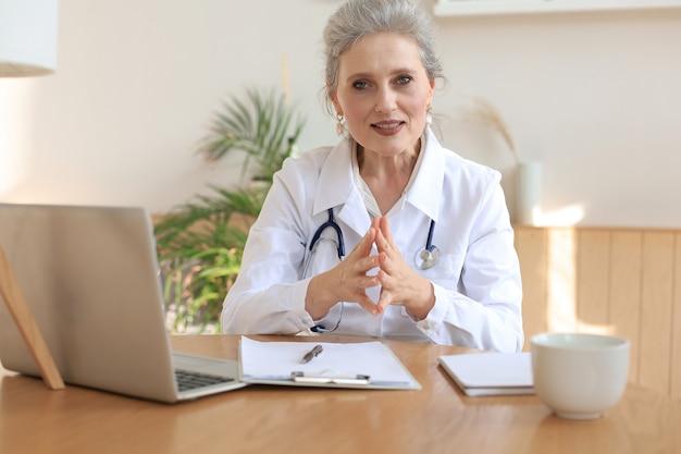 Пожилая женщина-врач-терапевт, носящая видеозвонок с гарнитурой, разговаривает с веб-камерой, консультируя виртуального пациента онлайн с помощью чата по видеоконференции.