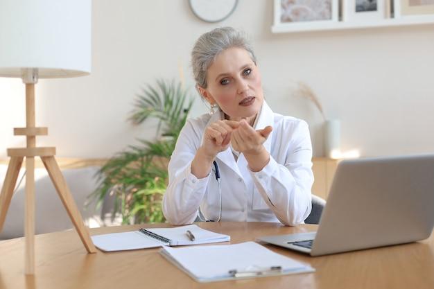 헤드셋 화상 통화를 착용한 나이든 여성 의사 치료사는 화상 회의 통화 채팅을 통해 온라인으로 가상 환자에게 상담하는 웹 카메라와 대화합니다.
