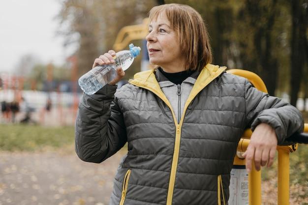 Пожилая женщина пьет воду после тренировки на открытом воздухе