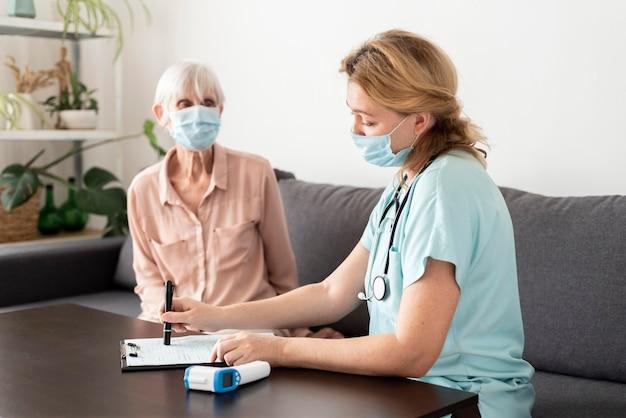 Donna anziana che ottiene il suo controllo con un'infermiera