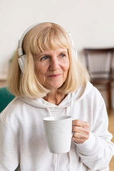 Пожилая женщина пьет кофе и слушает музыку в наушниках