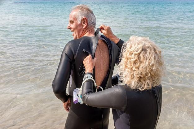 남편이 수영 여행을 위해 해변에서 잠수복을 입도록 돕는 나이든 여성