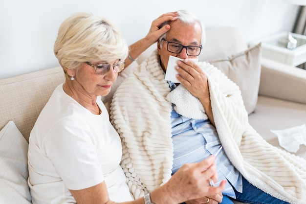 An older woman helps a ill husband
