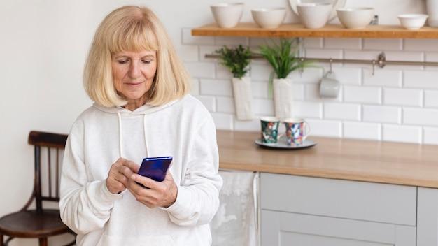 Donna anziana a casa utilizzando smartphone con copia spazio